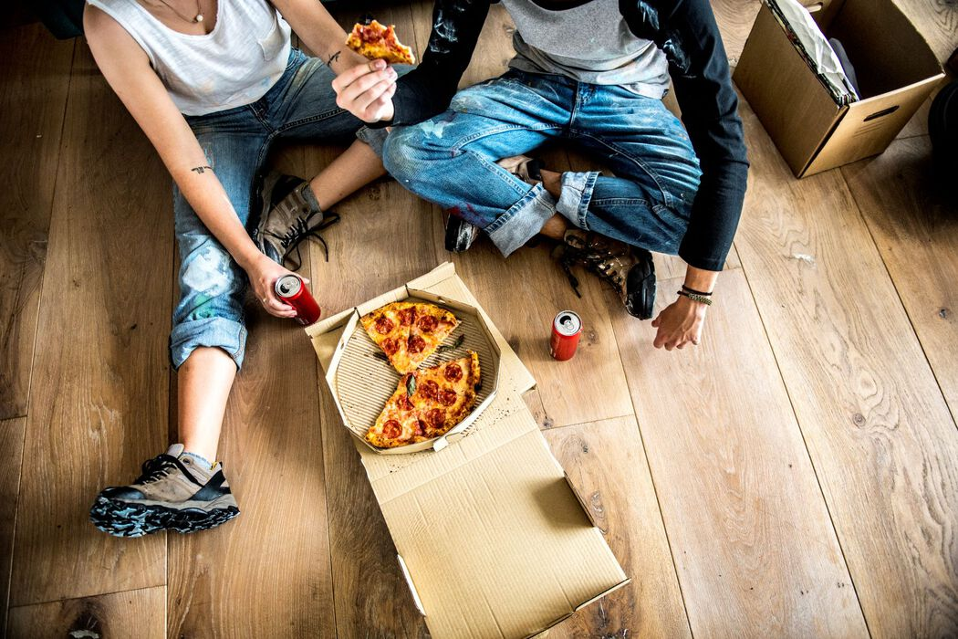 Couple eating pizza while moving and renovating