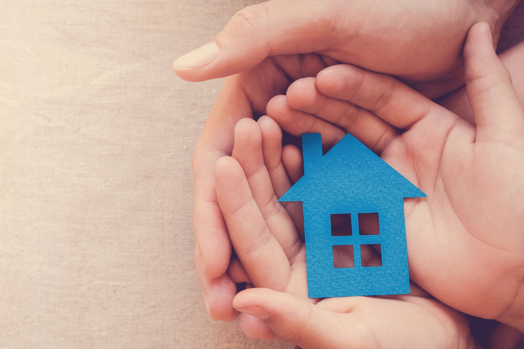 Two sets of hands cradle a blue paper cut-out of a house