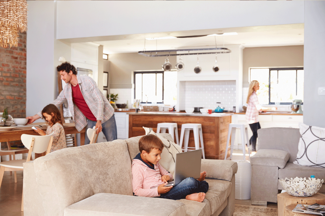 Family doing various activities in an open-concept home.