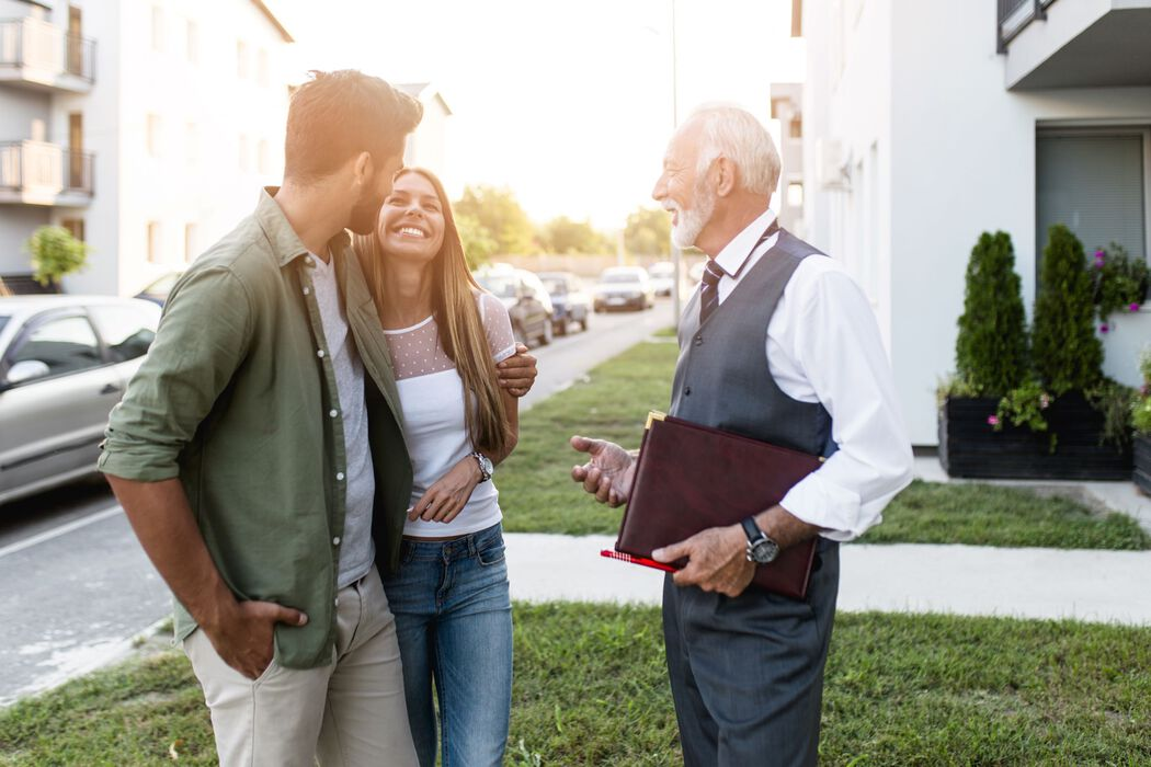A young man and woman look happily at each other in conversation with a real estate agent