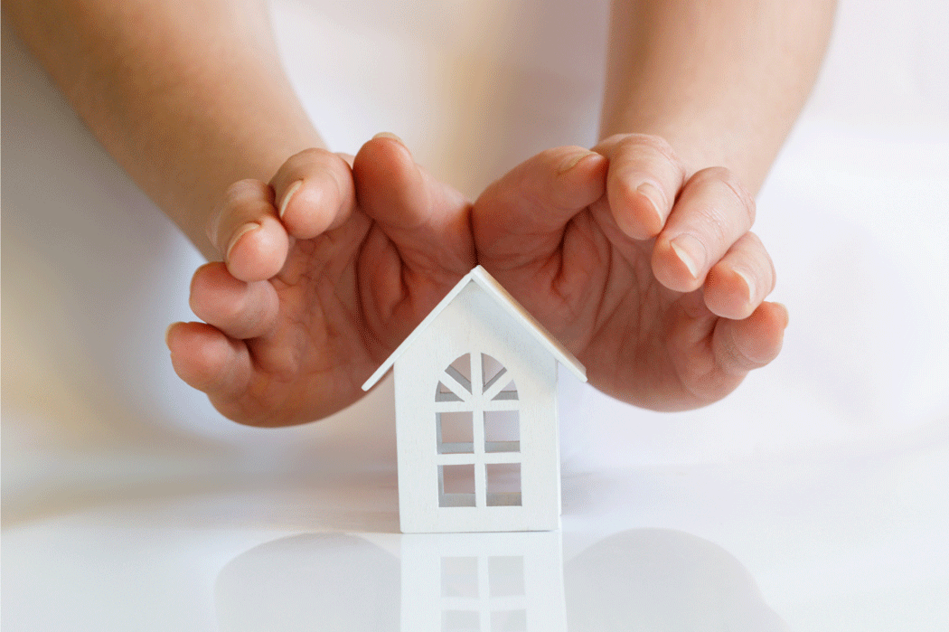 White paper house with a woman's hands hovering protectively above