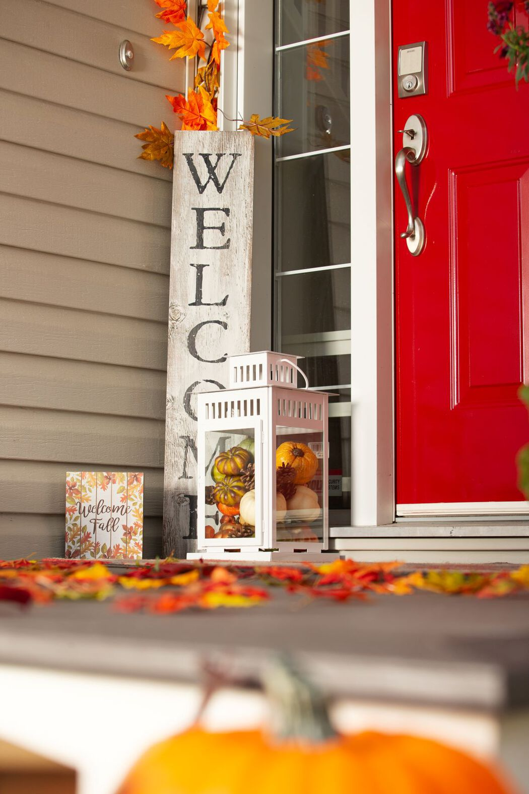 Red front door exterior with fall leaves, pumpkins, and welcome sign