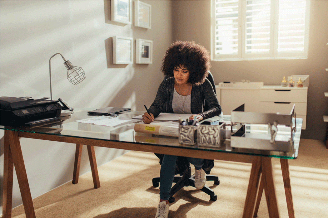 Woman at work in a home office, looking serene and focussed.