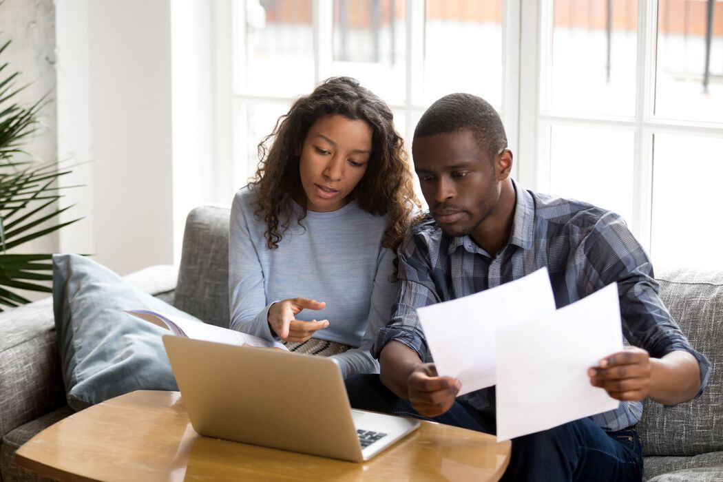 Couple looking over papers with laptop