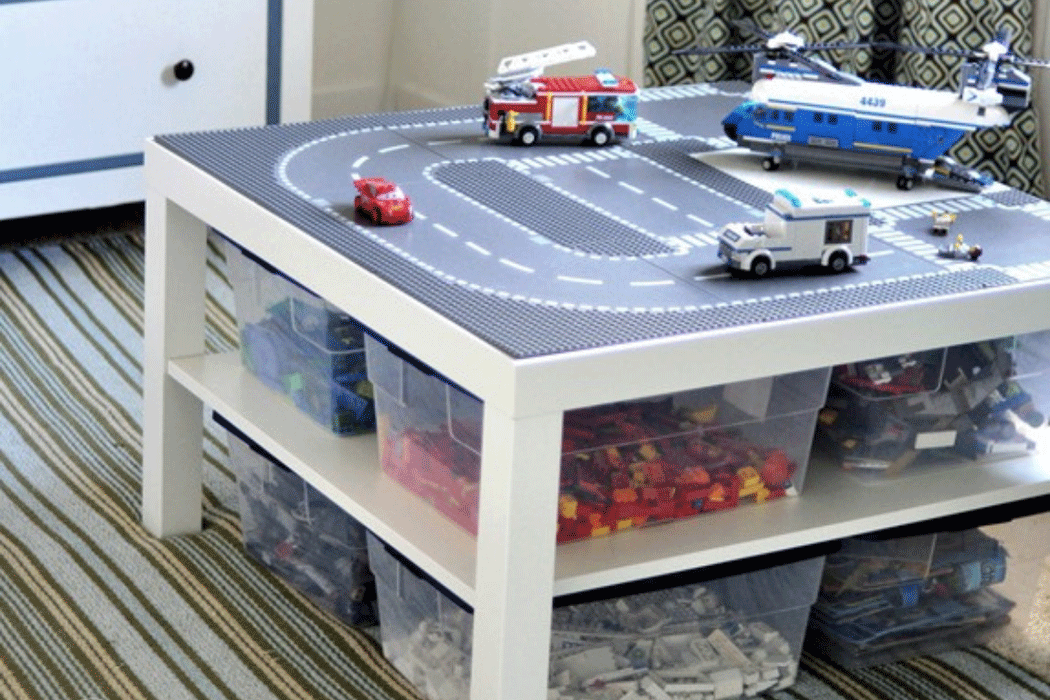 Play table with track on top and storage bins filled with Legos on shelf beneath