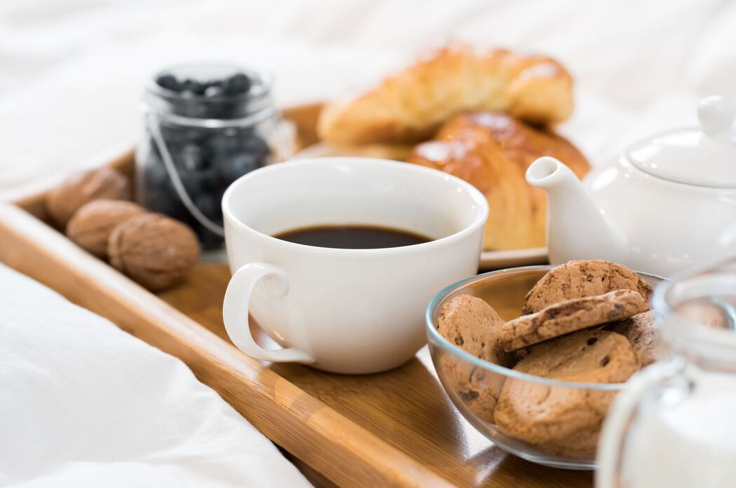 Breakfast in bed with tea, croissants, and cookies
