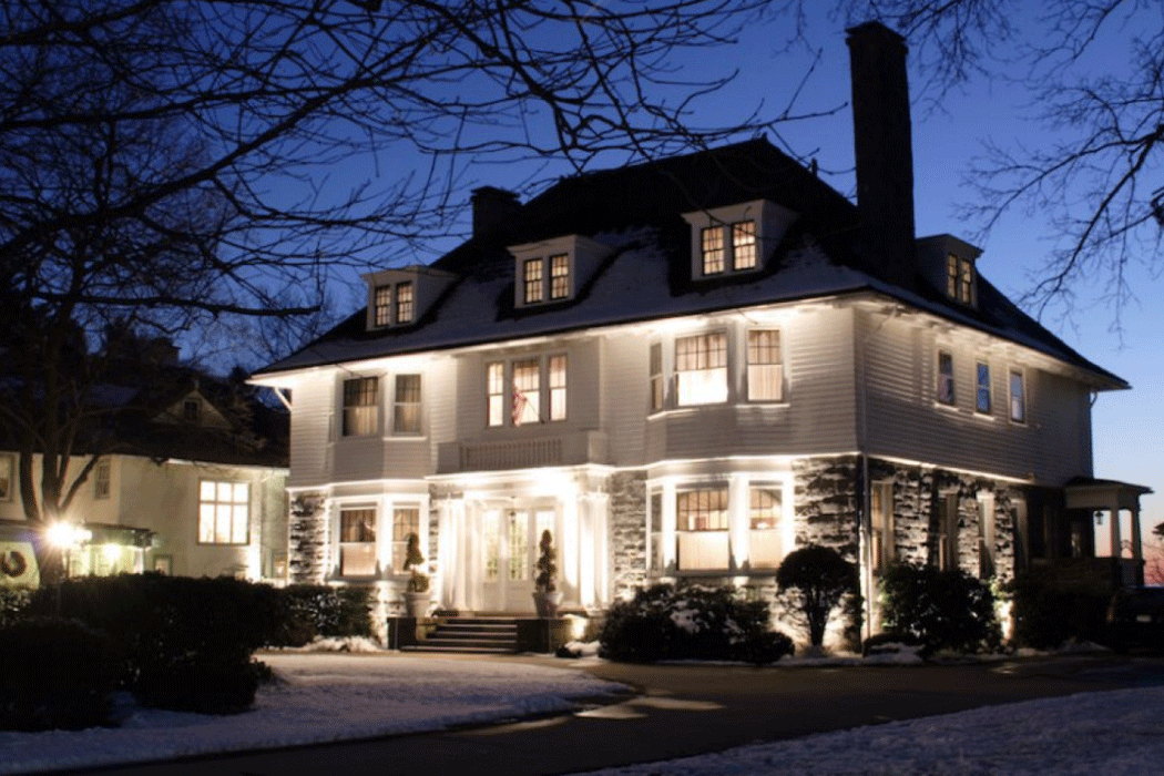 White sided house in the winter at night, illuminated by ground floodlights
