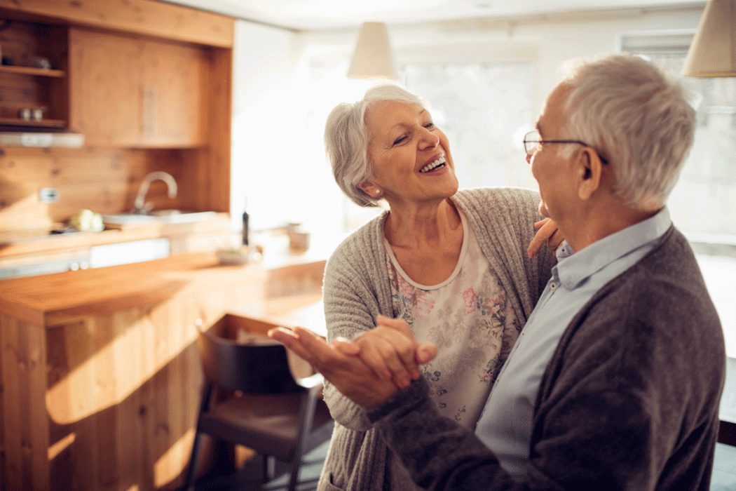 Elderly couple smiling and dancing in a sun-filled kitchen