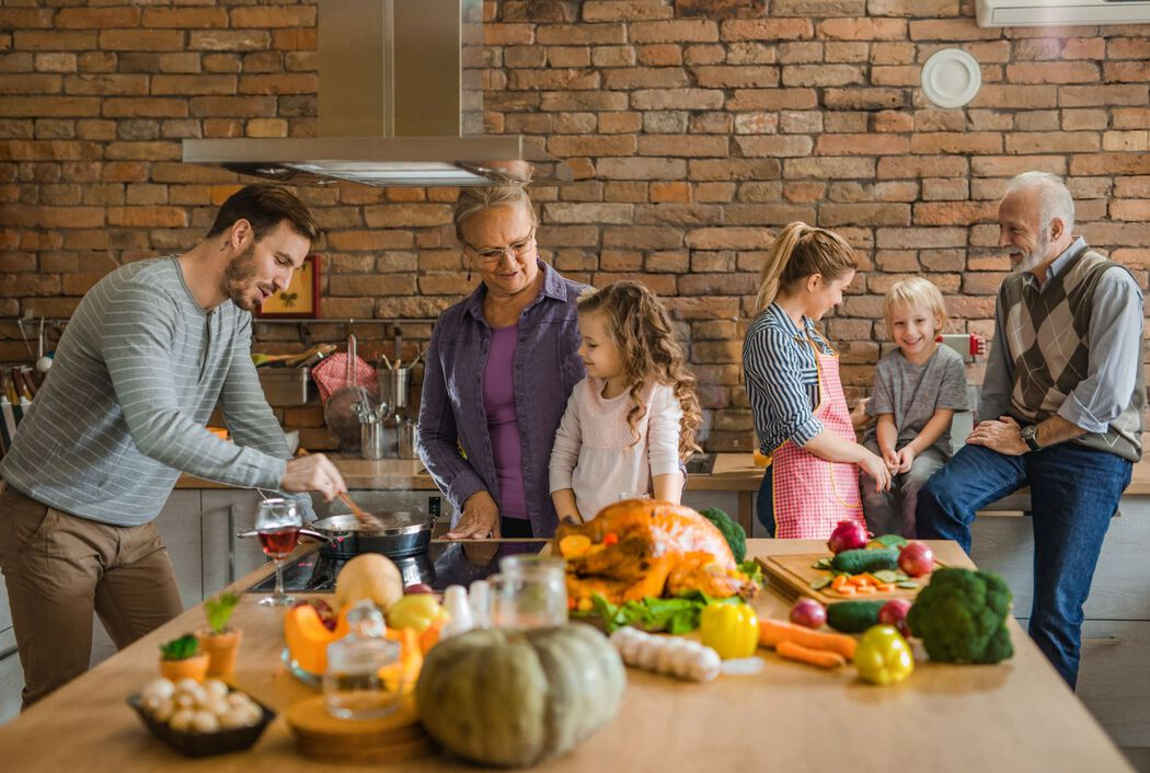 Multi-generational family in kitchen preparing a holiday dinner