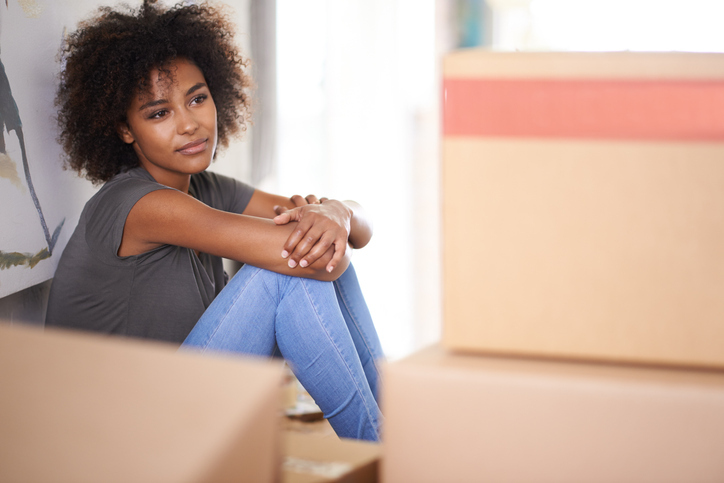Homebuyer sitting among boxes considering the future
