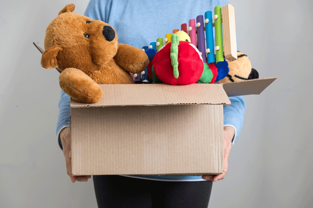 Woman holding cardboard box full of old toys