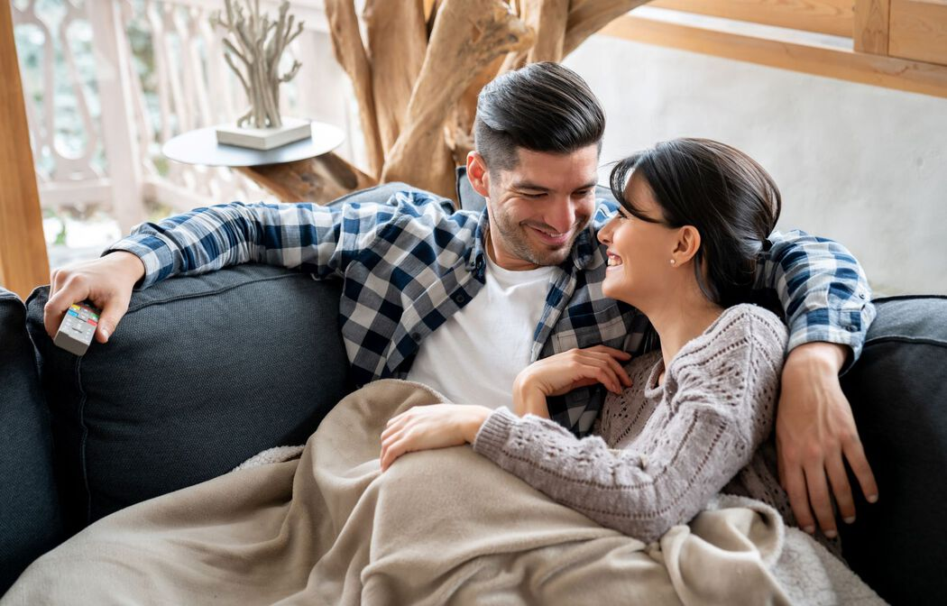 couple cuddling on couch under blanket