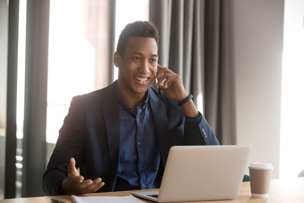 Young male agent smiling, talking on phone in front of laptop