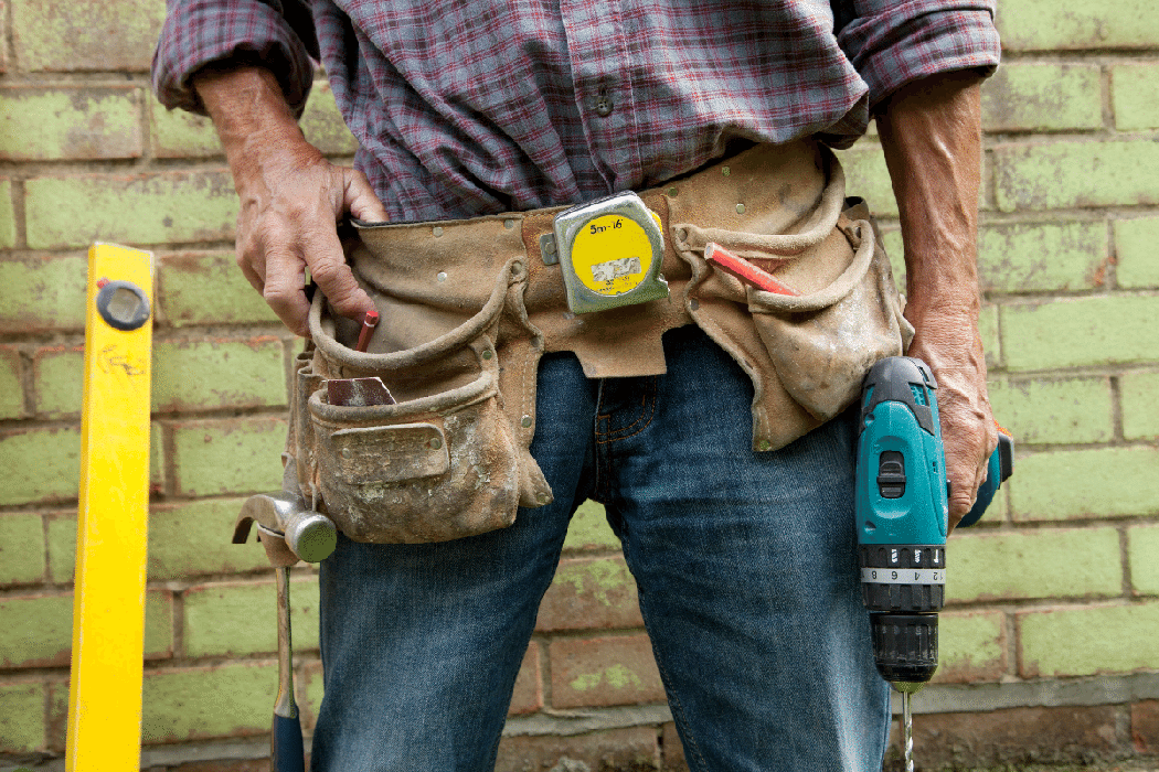 Mature man wearing a toolbelt for home renovations