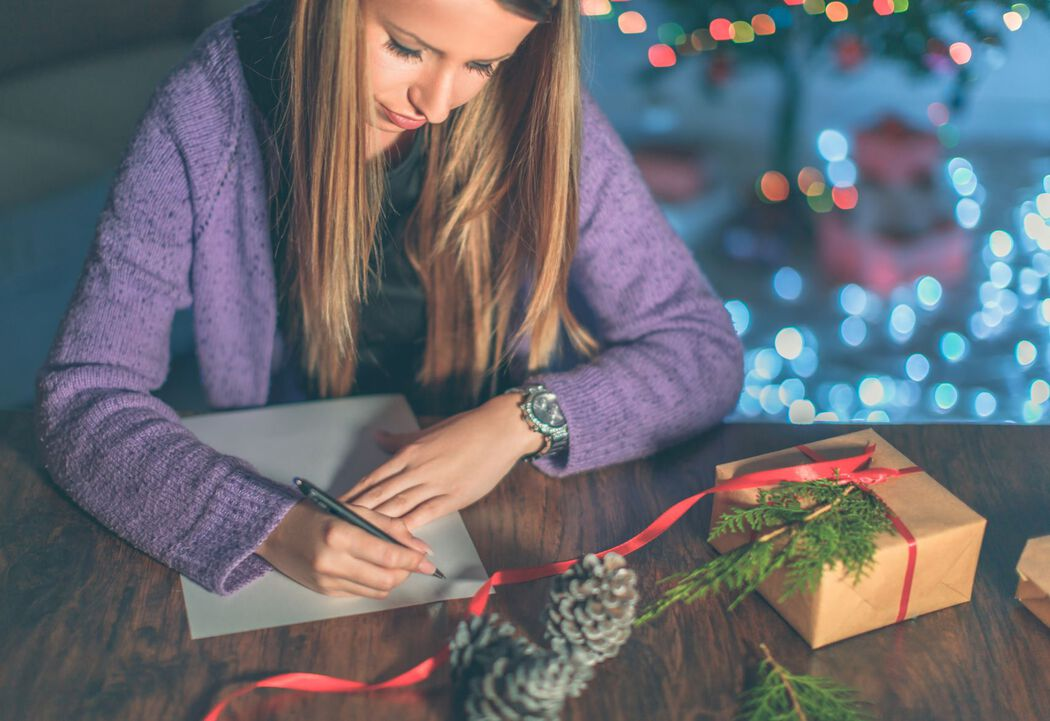 Girl writing letter while wrapping presents