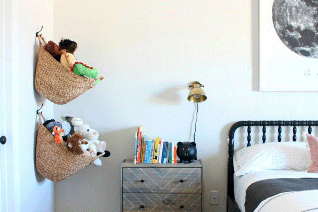 Wicker baskets filled with stuffed toys, hanging from hooks in a young person's room