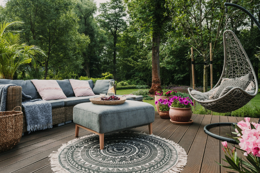 Furnished deck with carpet, swinging seat, flowers and lush greenery