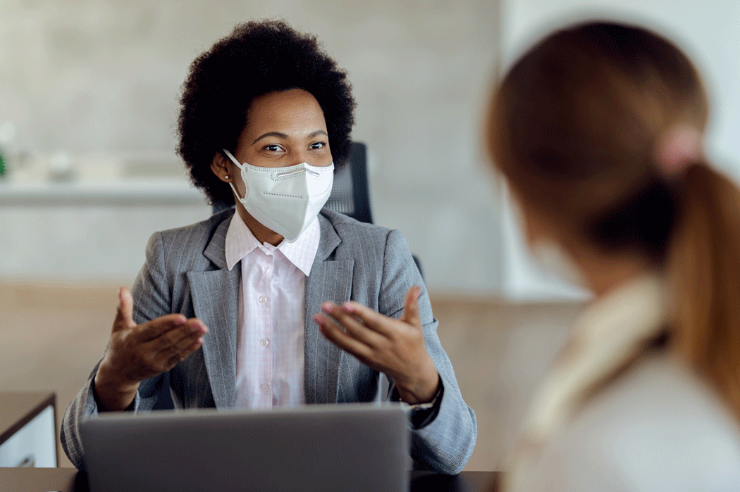 Smiling REALTOR® wearing PPE in discussion with client.