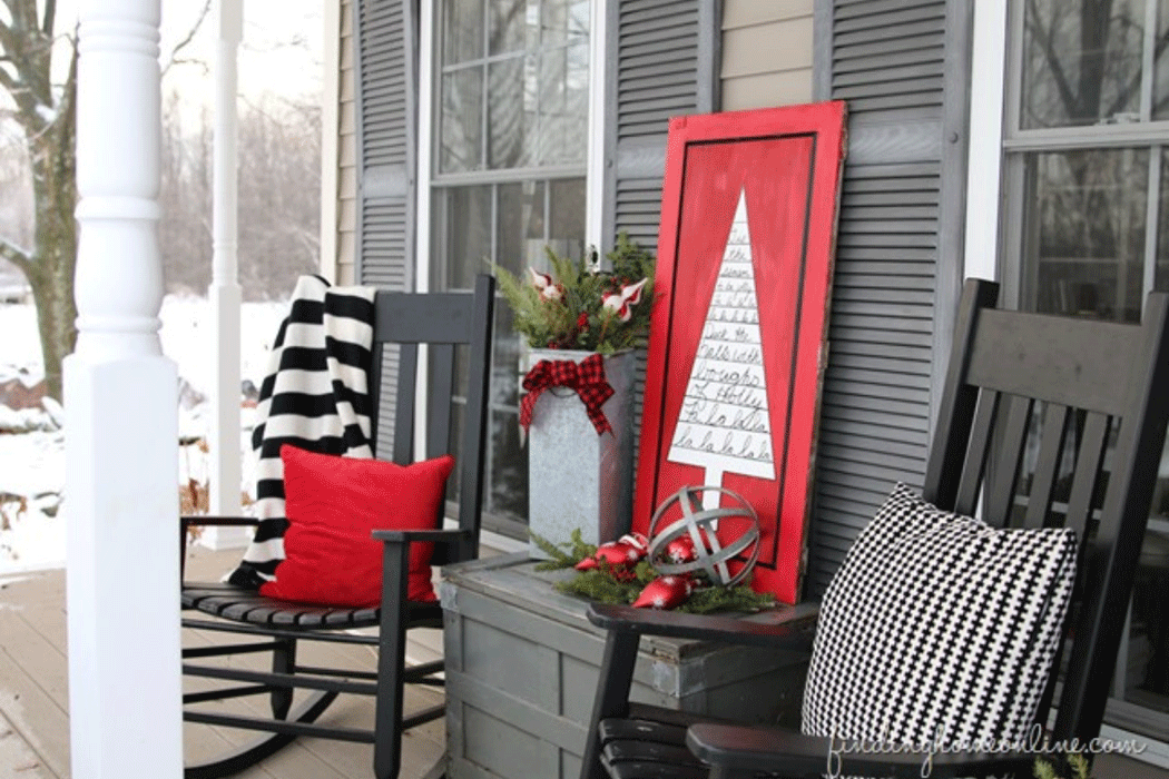 Two rocking chairs with cushions on a winter-time porch, with a table between them decorated for the holidays