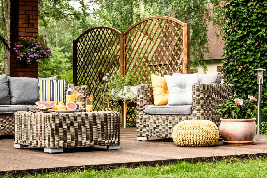 Outdoor patio with potted flowers and lawn furniture featuring multi-coloured throw pillows