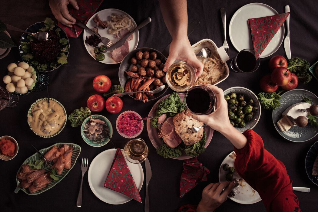 Christmas tablescape with food. Couple clinking glasses together.