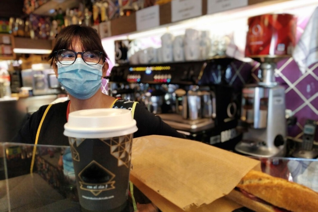 Woman in the food services industry stands behind a coffee counter wearing PPE