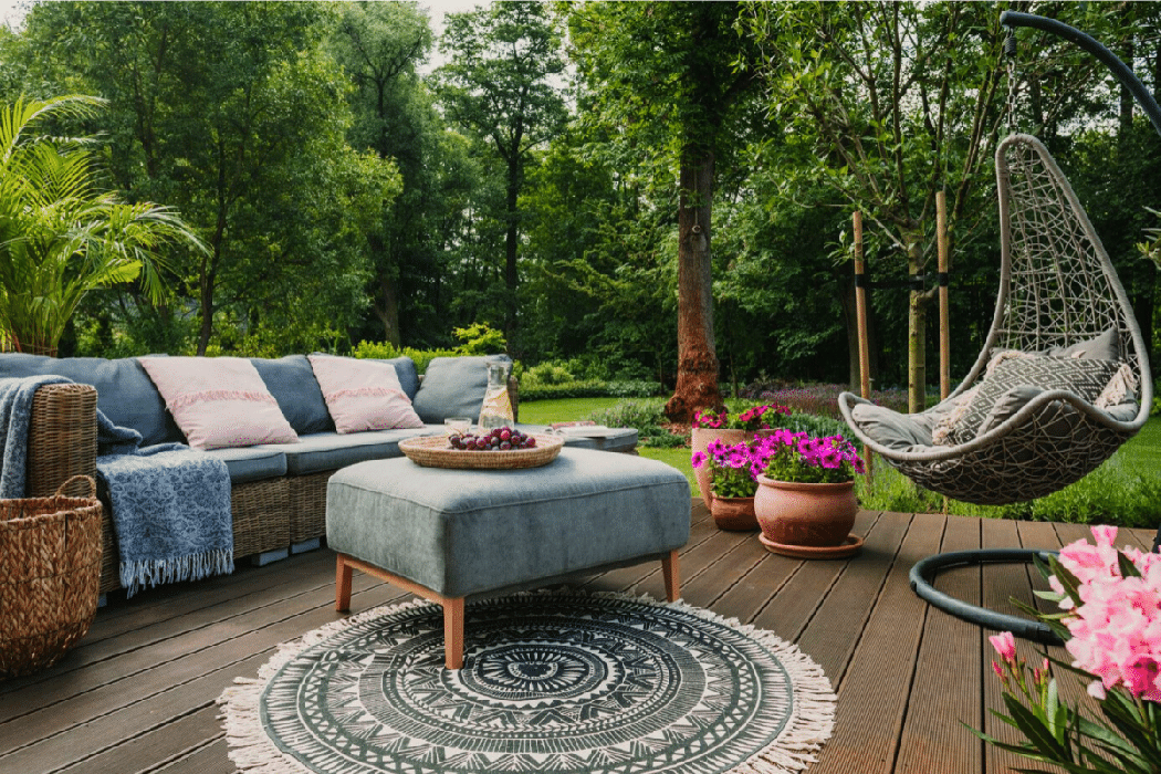 Backyard deck with comfy lawn furninture, bright flowers, and backdrop of mature trees