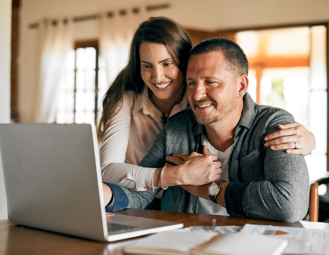 Middle-aged couple looking happily at a laptop