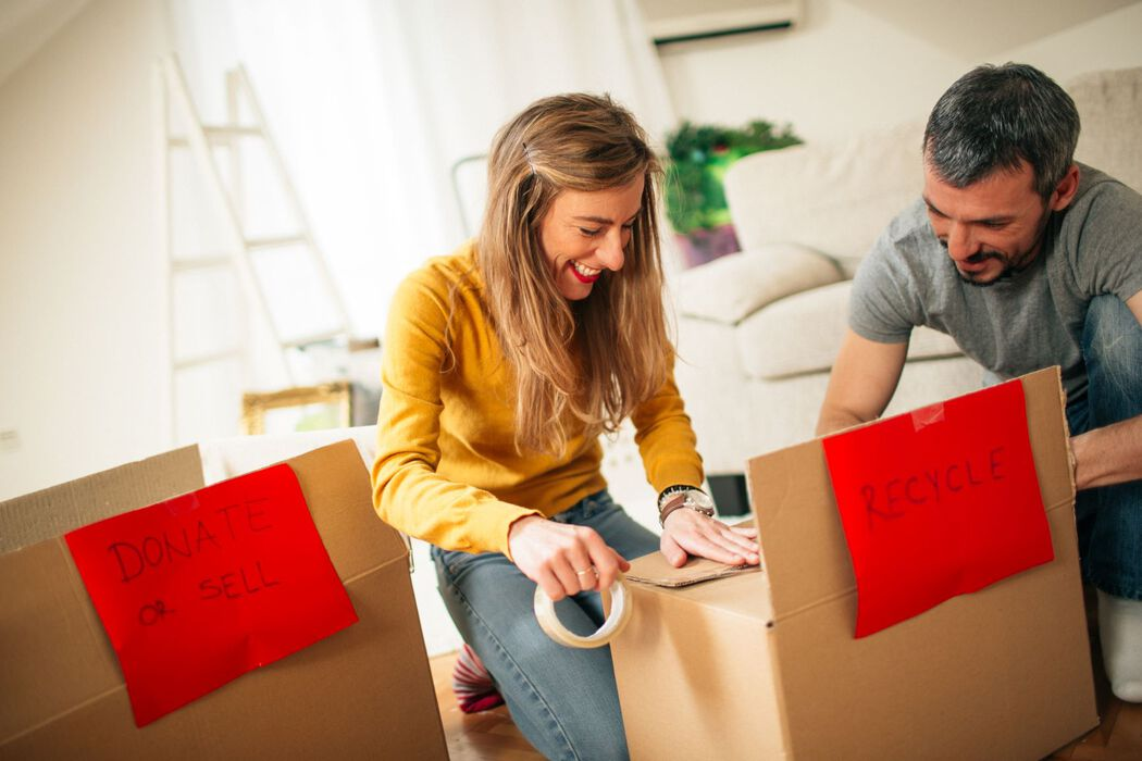 Couple organizing items into donation and recycle boxes