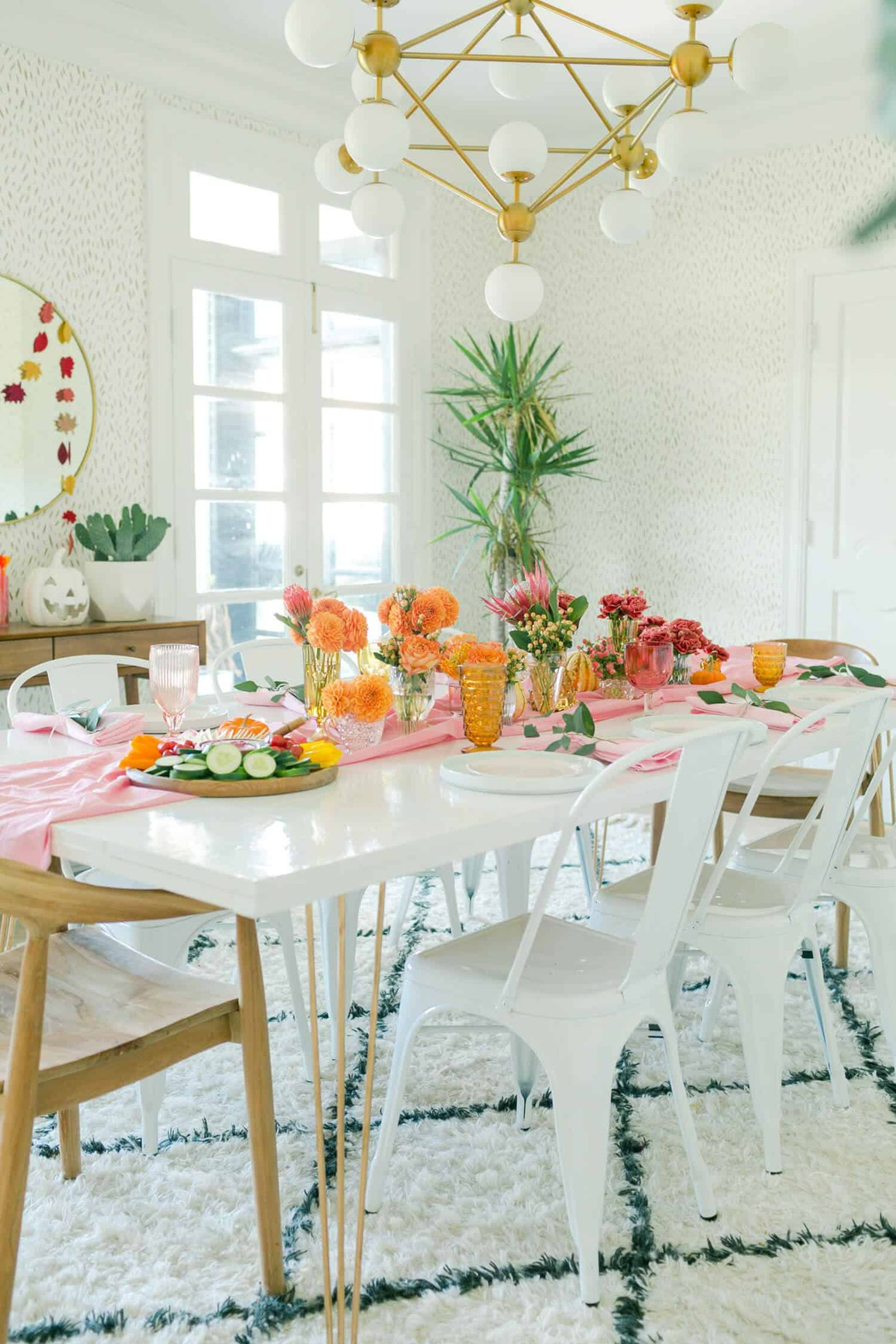 Thanksgiving tablescape with a pink runner, coloured glassware, and orange and magenta flowers