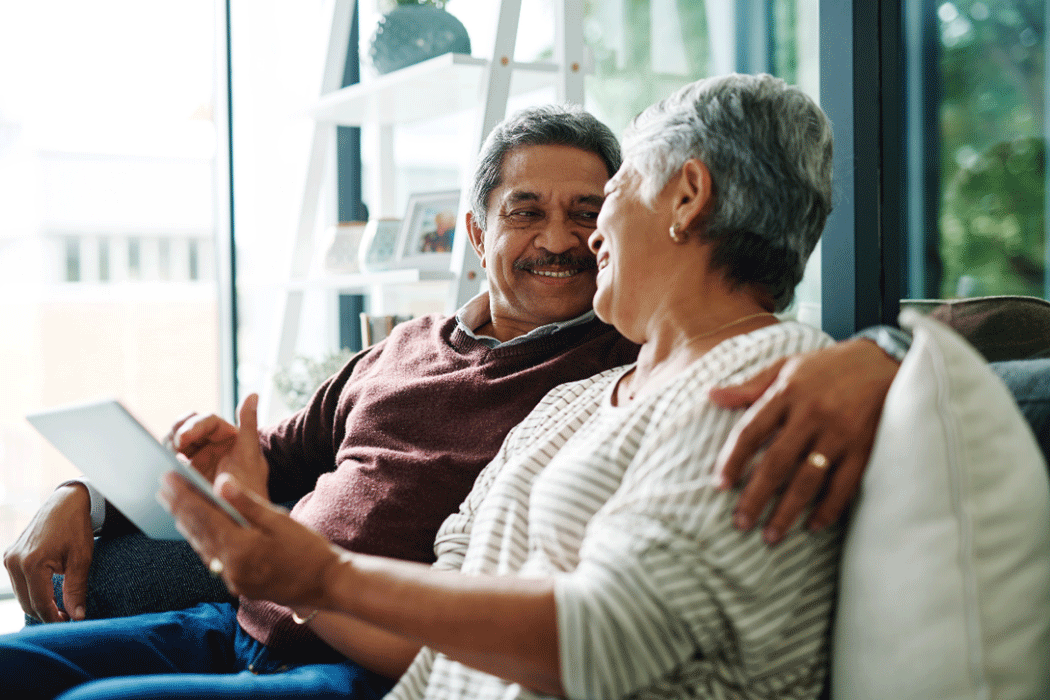 Elderly couple sitting on a sofa, holidng a tablet and smiling at each other