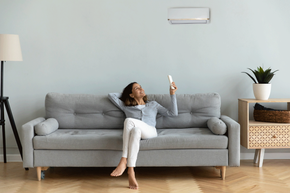 woman enjoying air conditioning while sitting on a grey sofa