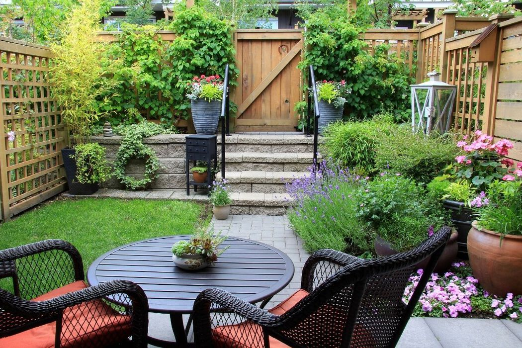 Small, landscaped backyard with potted flowers
