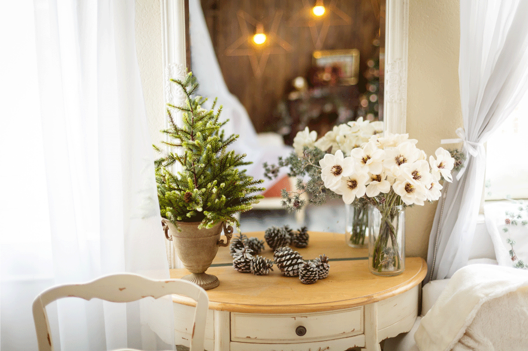 Adding flowers for your winter home sale: side table with a miniature pine, a bouquet of white flowers, and pine cones.