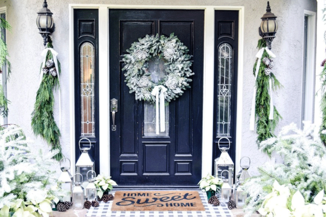 Front door with holiday wreath, flanked by silver candle lanterns, white poinsettias, and pine cones