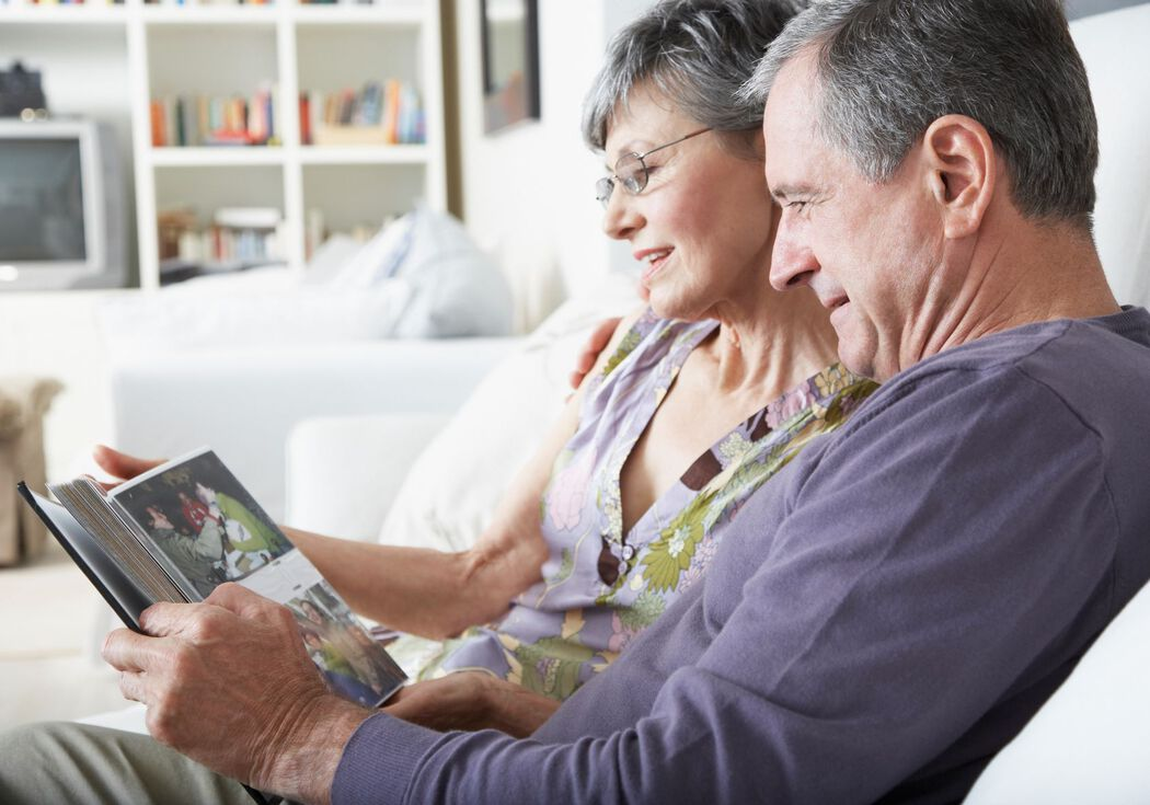 Middle aged couple looking at a photo album