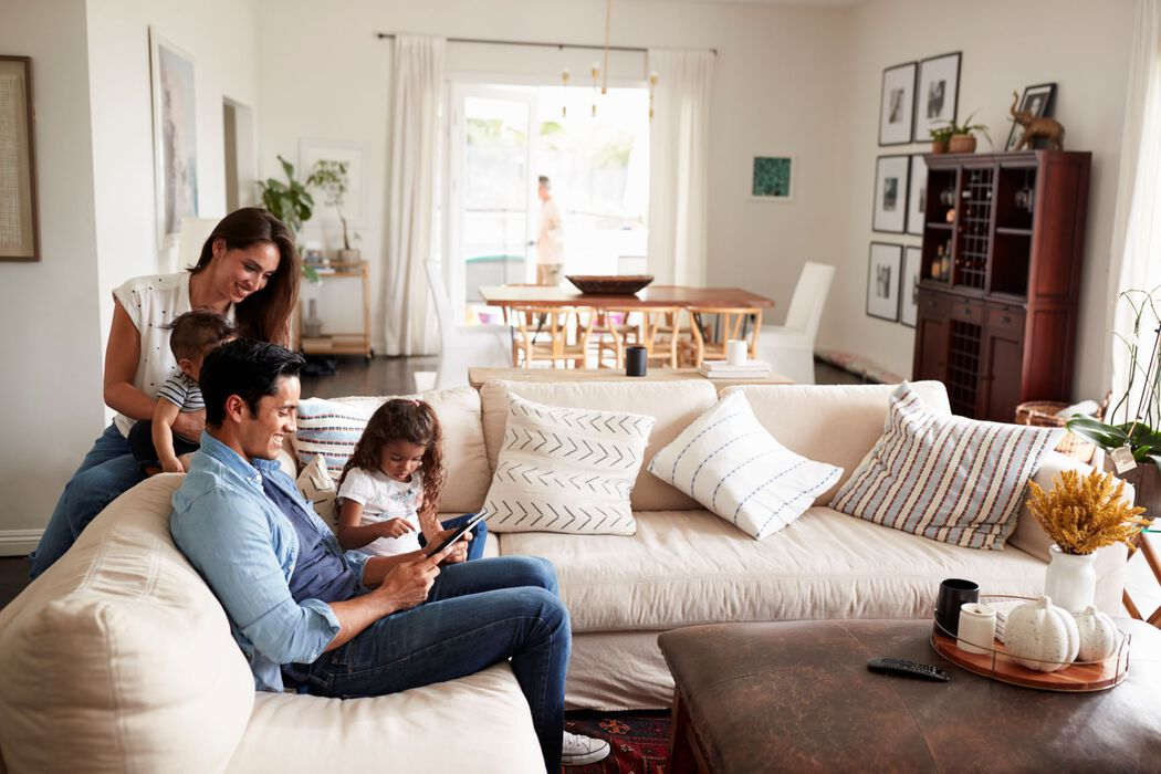 Family of four in living room looking at tablet