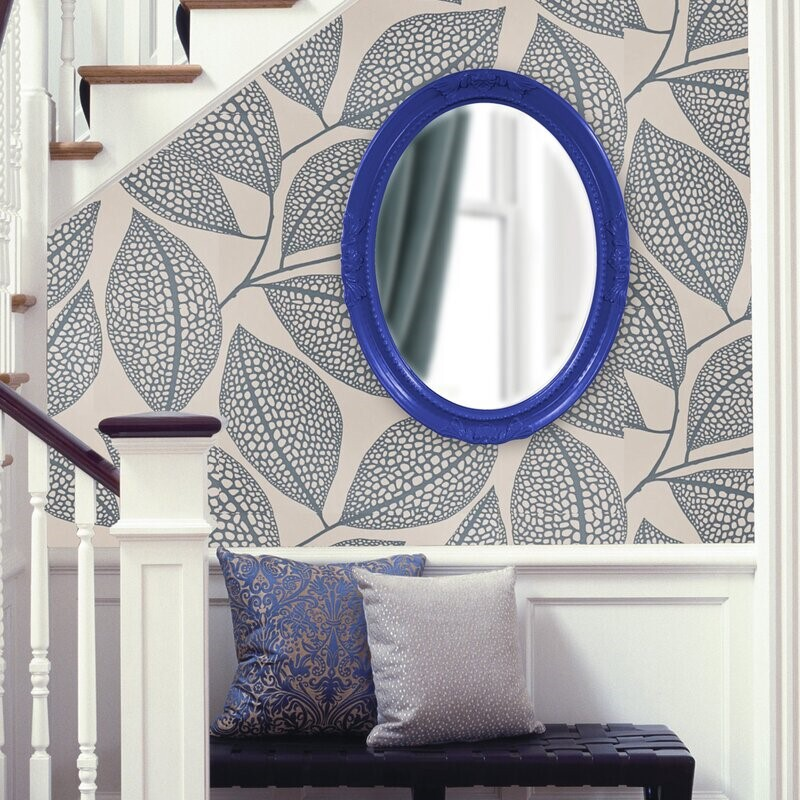 Blue mirror on wallpapered wall
