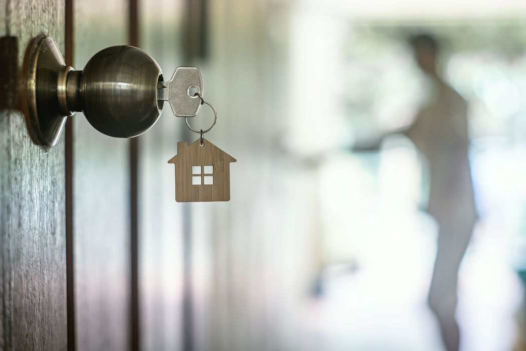 Doorknob with key in it, attached is a house-shaped keychain