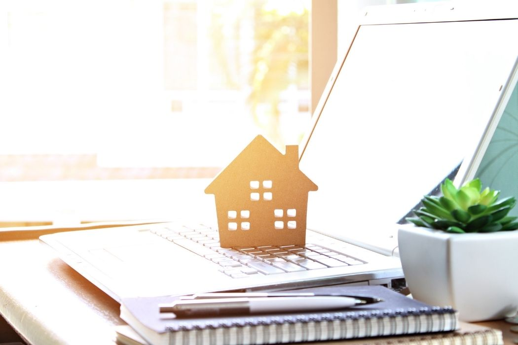 Small wooden house placed on an open laptop representing the search for a home