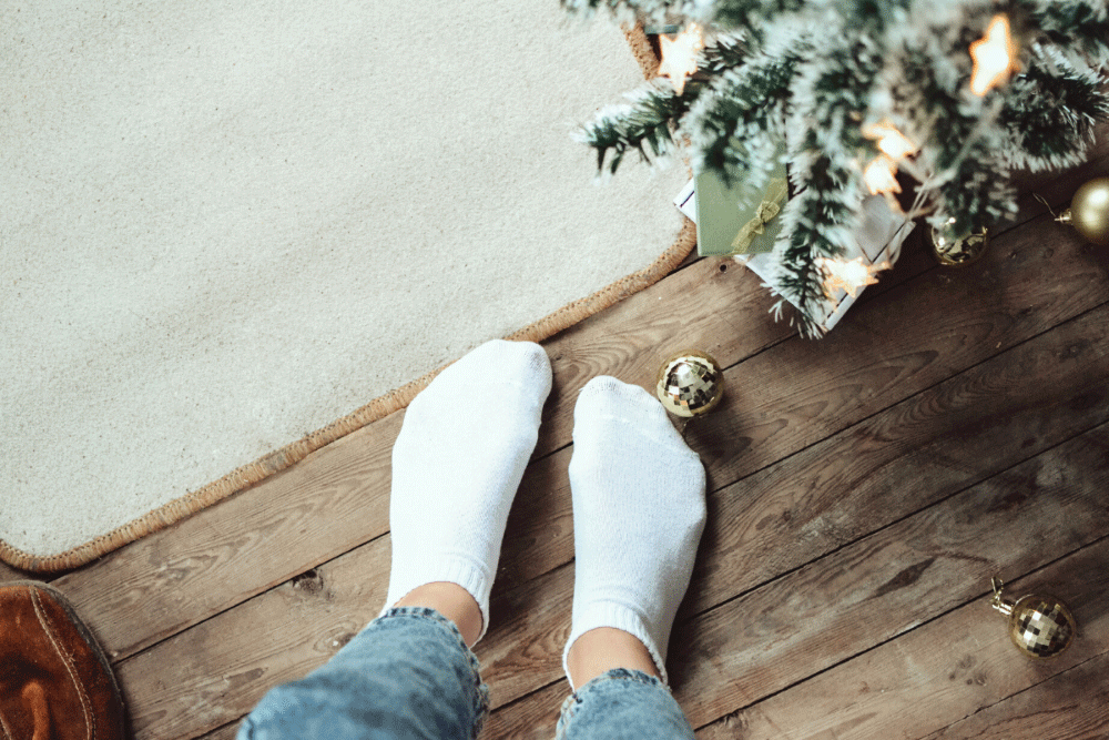 sock feet standing near a floor mat with some christmas tree boughs in the frame