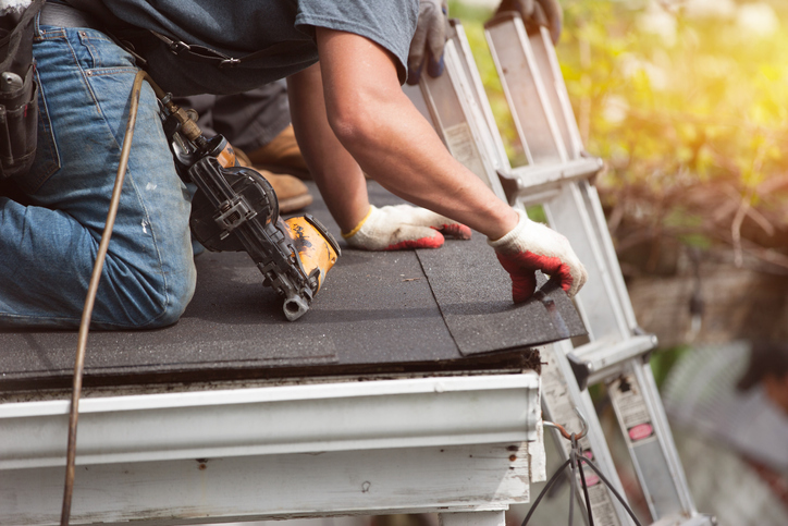 Homeowner putting on new shingles to increase the value of his house