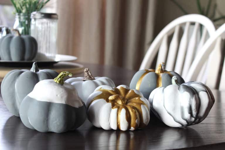 Miniature pumpkins painted grey, gold and white on a tabletop
