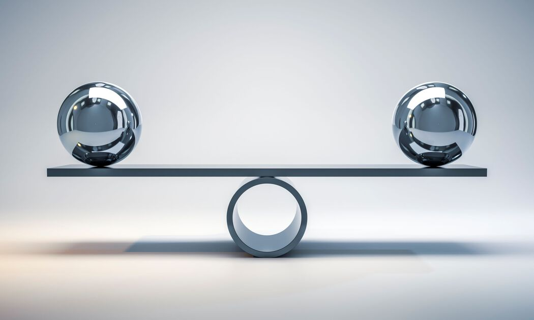 Two chrome balls sit at either end of platform that is balancing on a cylinder (abstract)