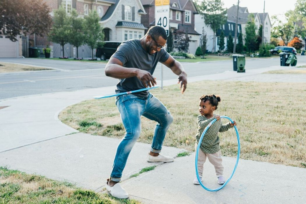Man and young child play hula-hoop on the sidewalk in a residential neighbourhood.