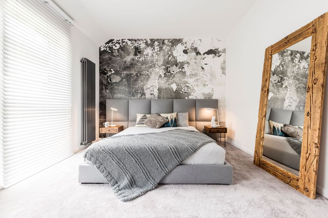 Master bedroom in gray and white with a large mirror