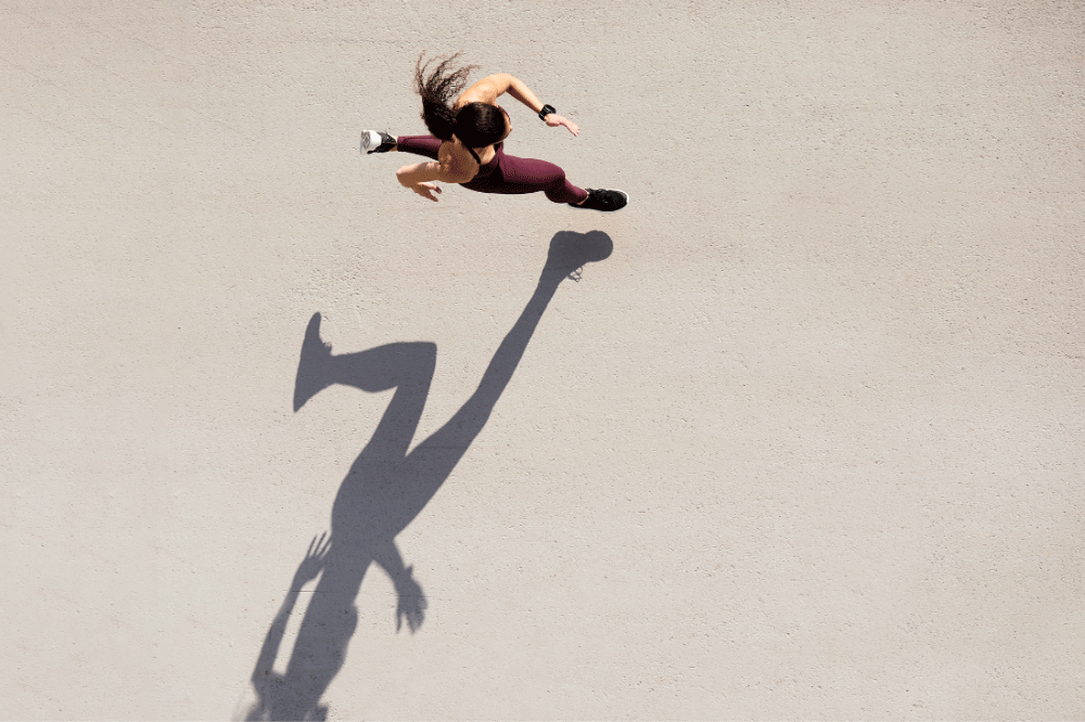 Aerial view of a woman running on pavement
