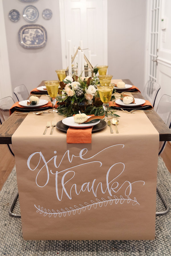 Thanksgiving tablescape with a paper runner, orange linens and mini white gourds on the place settings