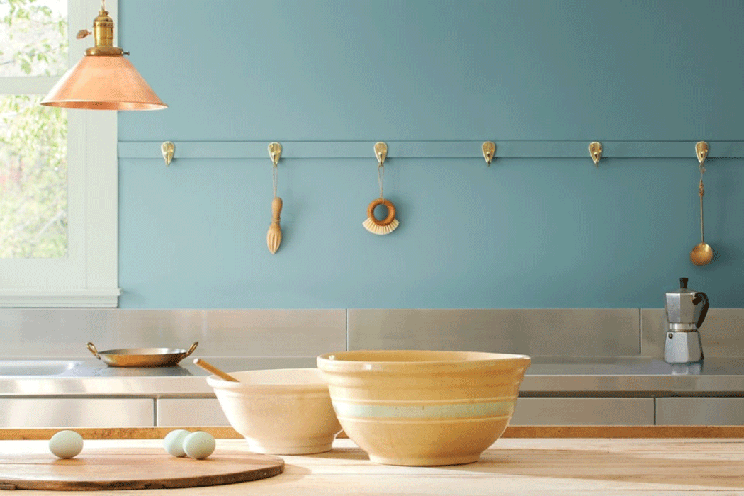 Sunny kitchen painted in Aegean Teal with yellow bowls on a wooden countertop