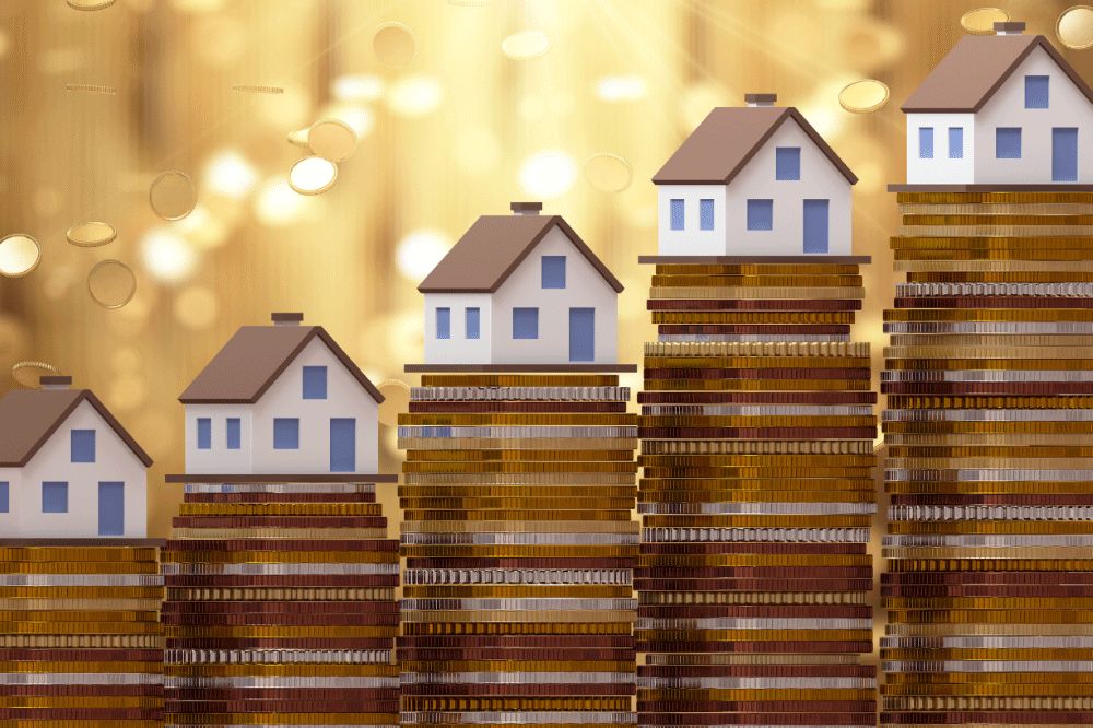 Image of toy houses sitting atop a row of stacked coins, each stack getting a bit higher than the last